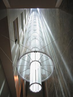 A roof-mounted heliostat (sun-tracking mirror) directs light down a 14-story atrium. The light is directed outward by a tapering tube of prismatic glass, and diffused by stretched fabric