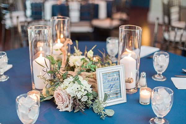 Coastal wedding centerpiece ideas with candles, driftwood, and table number