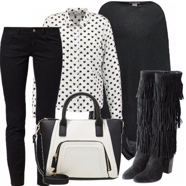 Jeans skinny in denim nero , camicia bianca con stampa a cuore, mantella nera con frange, stivali alti con tacco quadrato e frange, borsa a blocchi di colore