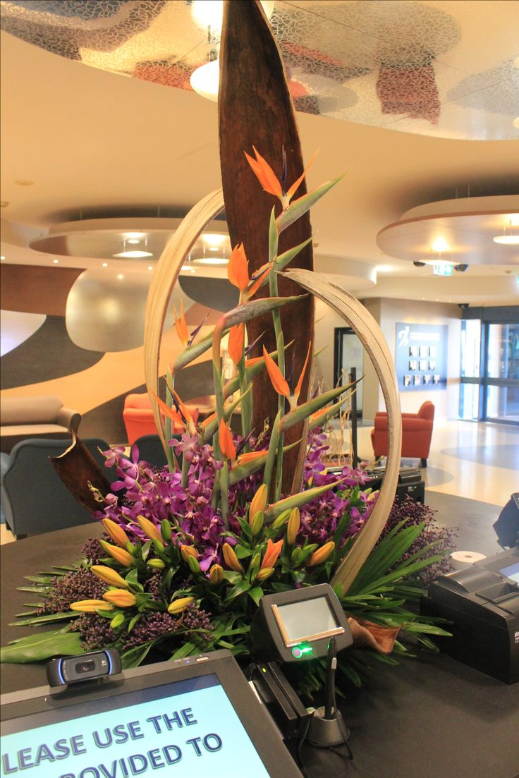 Large Tropical Floral arrangement with Bird of Paradise, Orchids, Lily and Palm Husks. Created by Poppies and Peas Floral Design.