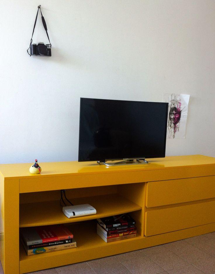 Sala: rack amarelo, tv, livros, ilustração inacabada e ...