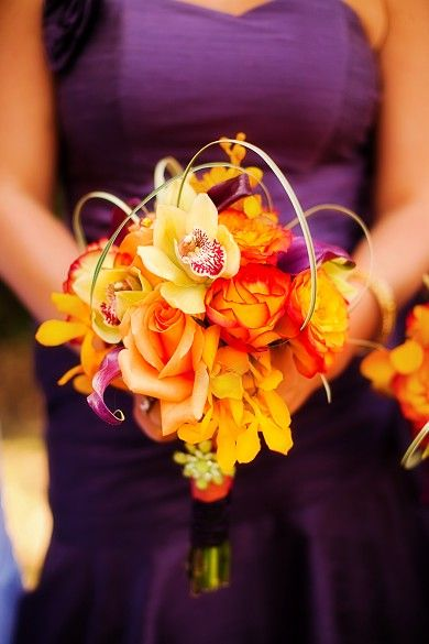 Fall Harvest Bridesmaid Bouquet in orange, red, purple & green~ circus & salmon roses, orange mokara orchids, green cymbidium orchids, purple miniature calla lilies and variegated lily grass  Photography Credit~ Schaap Studios