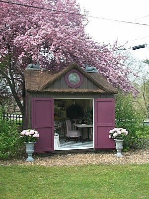 This garden shed is so wonderful -- the gable, round window, shutter-style doors and pairs of urns.  Pairs: good.
