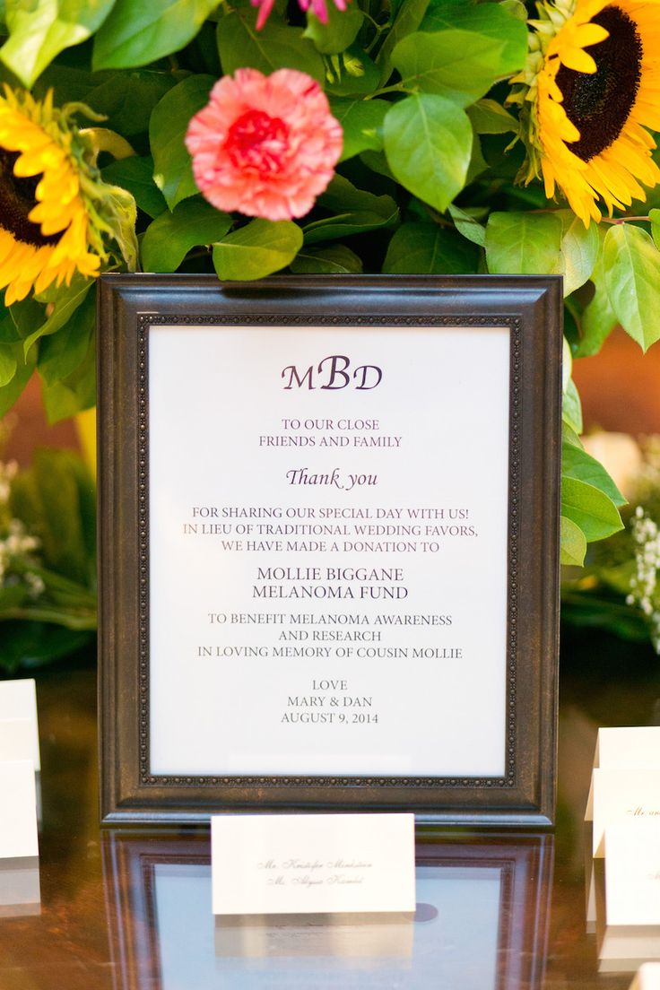 In lieu of wedding favors, a sign in a dark-wood frame informed guests that Mary and Daniel had made a donation to the Mollie Biggane Melanoma Fund. #donation #weddingfavoridea Photography: Cassi Claire Photography. Read More: http://www.insideweddings.com/weddings/casually-chic-country-club-wedding-in-new-york-with-pastel-details/662/