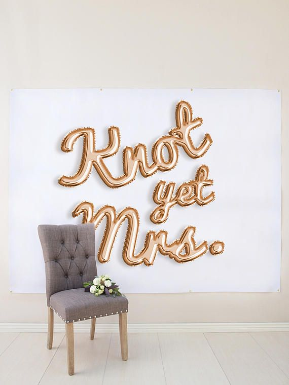 "This rose gold balloon letters backdrop is perfect for a bridal shower or bachelorette party, and reads ""knot yet mrs."""