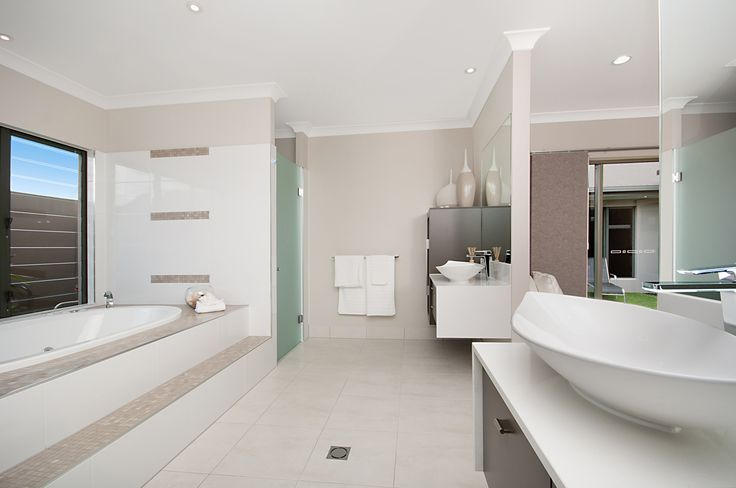 Bathroom by David McCoy Homes with double vanities, large central bath area, as well as frosted glass doors to hide the shower and toilet.
