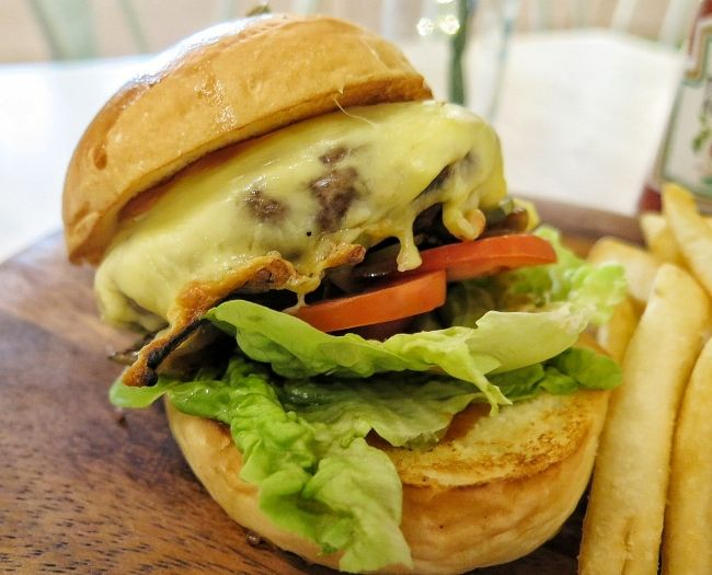 """""""Dream"""" burger. A 10 oz patty of premium USA black Angus beef -- seared to a medium-rare, served on a house-baked brioche bun with caramelized onions, leaves of crisp Romaine, two slices of vine-ripened tomato and a generous piece of Gruyere. Served with a side of hand-cut fries."""