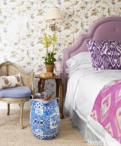 Lilac gets a reprise in the master bedroom of this New York City apartment, both in the custom headboard and the floral accents of the Hummingbirds wallpaper by Cole & Son. The bed is dressed in linens from Restoration Hardware, and the swing-arm light is from Vaughan. Pottery Barn's Duncan Diamond rug adds a neutral counterpoint to a room filled with pattern and color. Click through for more colorful decorating ideas from designer Mark D. Sikes's New York City apartment.