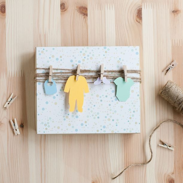 baby shower gift wrap: baby's things // Cut out baby clothes from heavy paper and tie or clip them on the wrapping yarn.
