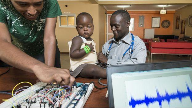 """Un niño usando la chaqueta para detectar neumonía y Brian Turyabagye (a la derecha). La chaqueta que detecta neumonía y otros ingeniosos inventos que llegarán de África en 2017. el ingeniero ugandés Brian Turyabagye ha diseñado una """"chaqueta inteligente"""" que detecta de forma rápida y precisa la neumonía. La llamó Mamaope y es capaz de medir la temperatura de un niño para saber si está enfermo y su frecuencia respiratoria."""