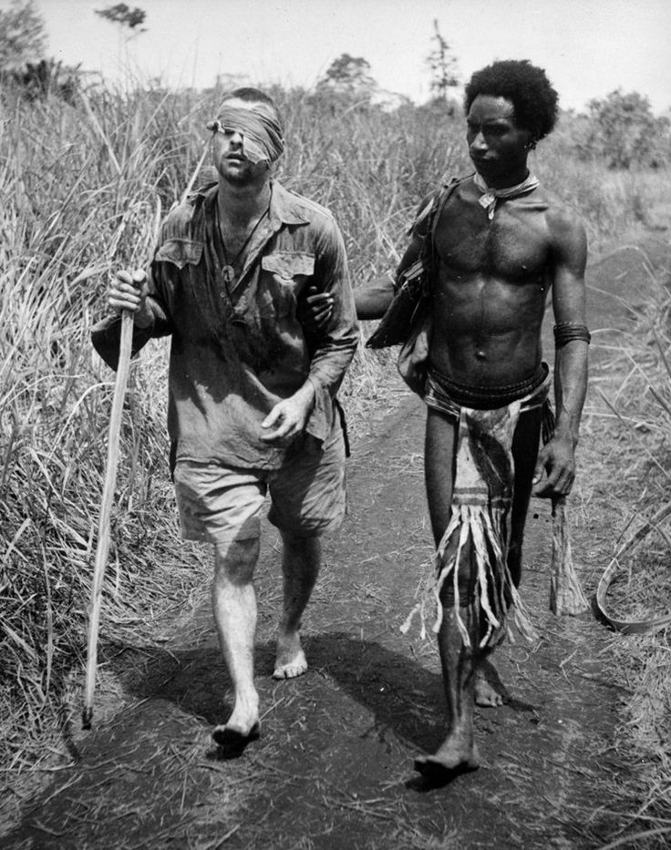 Christmas day 1942 New Guinea. Blinded soldier Pte George Whittington being led to an aid station by Raphael Oimbari - Photographer George Silk....