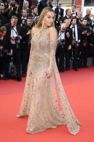 Cannes 2017: Rita Ora in versione odalisca, con abito dorato, spalle scoperte e lunghi nastri pendenti dalle  braccia firmato Elie Saab.