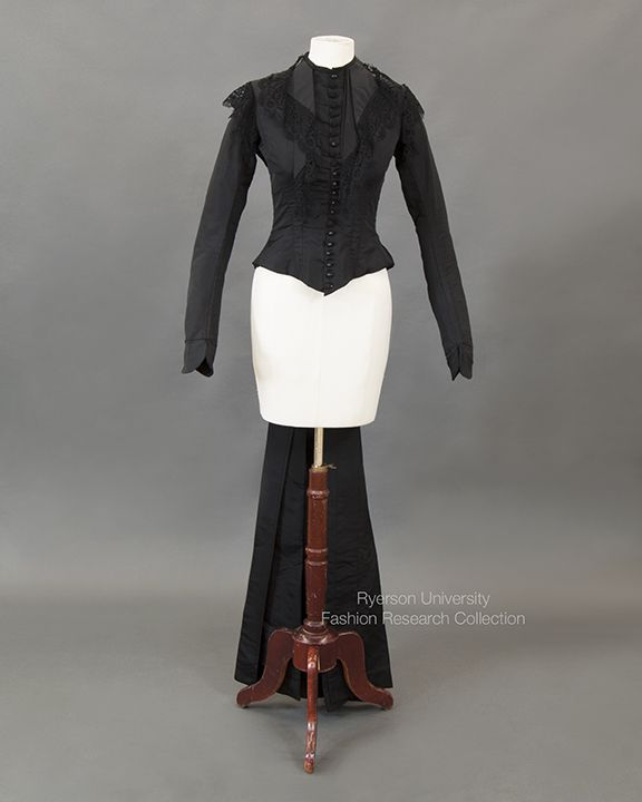 Black silk taffeta bodice with extended tails, interior boning, fuschia pink selvedge visible, jabot collar with machine lace detail, self-covered buttons (22), missing skirt. c.1878. FRC1999.05.001.