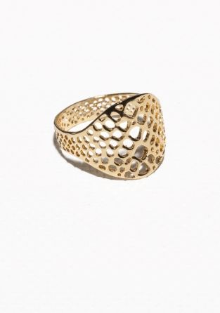Crafted from brass, this ring features a finely cut fossil design with delicate cut-outs.