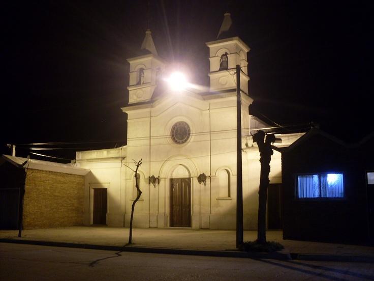 Una vista nocturna de la fachada iluminada de la Catedral de la ciudad de Nueva Palmira, Departamento de Colonia.