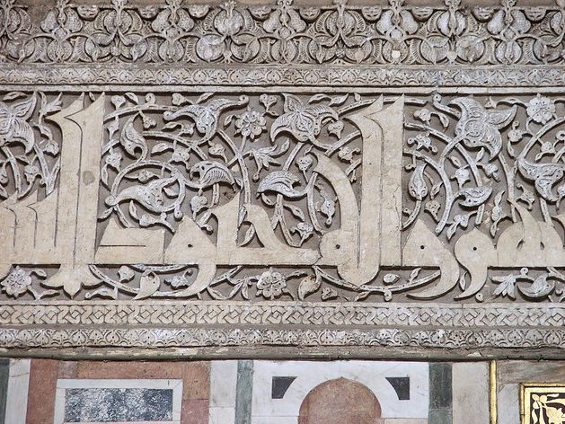 """Decorative ⁖Karmathian Kufic script rich in foliate 'horror vacui' cyclical infill resembling earlier Roman Byzantine mosaic decoration, Cairo Mosque facade http://islamic-arts.org/2011/styles-of-calligraphy/ aka ⁖Qarmatians Arabic قرمطي, """"those who wrote in small letters"""" (historical) a religious syncretism of Ismaili Shi'i branch of Islam with Persian mysticism, founded by Hamdan al-Qarmat, centered in eastern Arabia, where they attempted to establish a utopian republic in 899 CE."""
