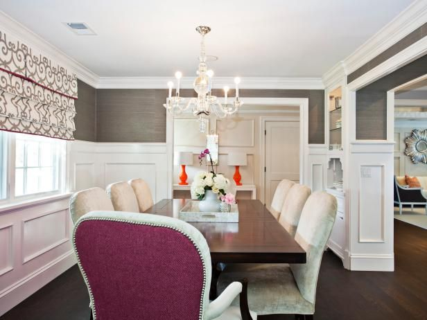 HGTV showcases a gray traditional dining room with upholstered chairs, crystal chandelier, wood dining table, and high wainscoting on the walls.