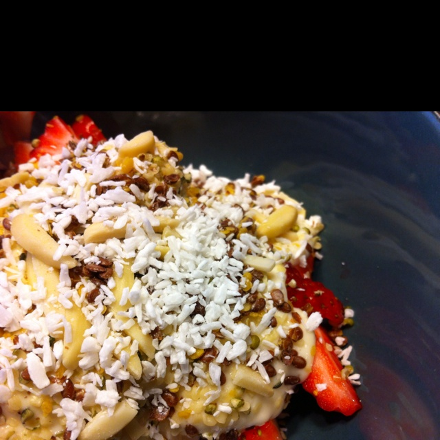 Sliced strawberries with pear cream topped with hemp seeds, flax seeds, slivered almonds and shredded coconut.