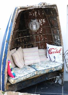 Great idea, upcycled boat as seat with gorgeous lamp and cushions.