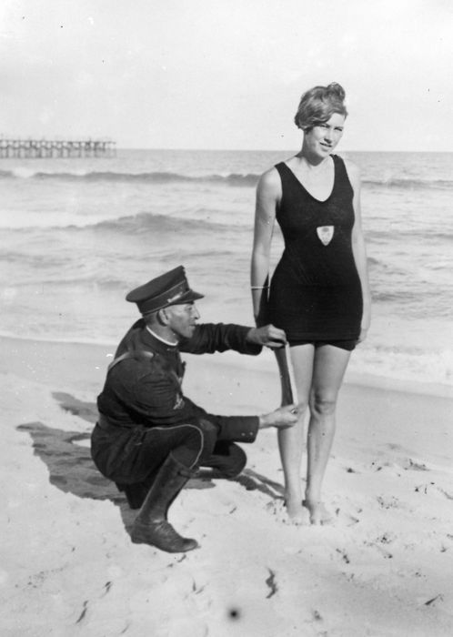 """Smokey"" Buchanan from the West Palm Beach police force, measuring the bathing suit of Betty Fringle on Palm Beach, to ensure that it conforms with regulations introduced by the beach censors. c.1925"
