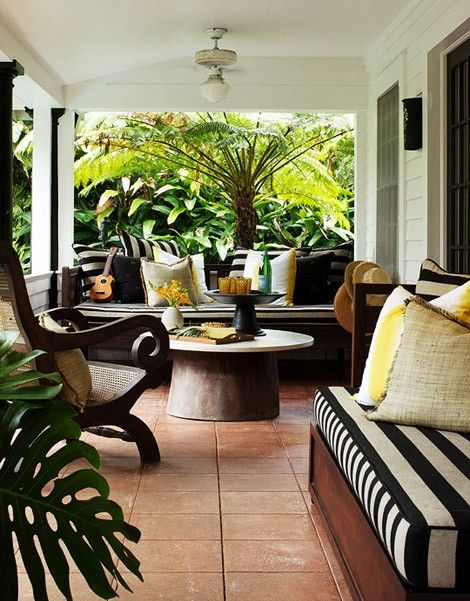 Black and white stripes may not be an obvious choice for coastal style, but when paired with bright yellow and leafy tropical plants, the result is chic and laid-back. For more ideas on Beach Cottage Style: Outdoor Spaces, go to http://decoratingfiles.com/2012/07/beach-cottage-style-outdoor-spaces/
