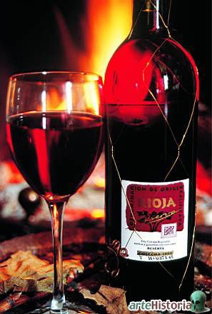 Spanish Rioja wine by the fire with a traditional wire cage that was originally designed to prevent restauranteurs from filling the bottle with cheap wine