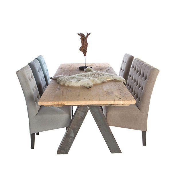 Het onderstel wat een omgekeerde V is in combinatie met het tafelblad wat bestaat uit een kleinere metalen onderkant met een grotere houten tafelblad. Wat voor een soort X vorming zorgt.
