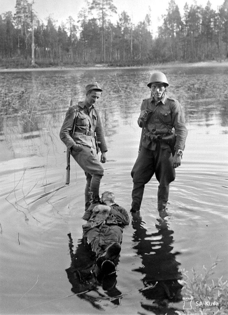 Finnish soldiers stand in lake Paanajärvi over the dead body of an enemySoviet soldier killed during the Finnish-Soviet Continuation War. Near Rukajärvi, Karelia, Finland (now Rugozero, Republic of Karelia, Russia). 31 July 1941.