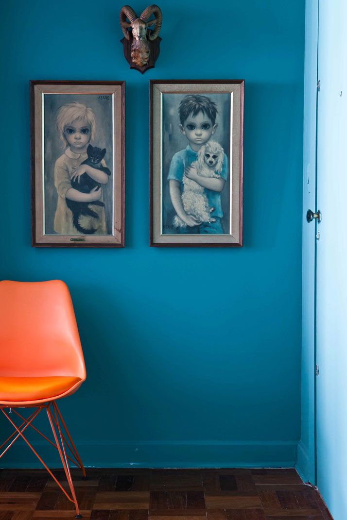 Brazilian DJ and Pil Marques in São Paulo, Brazil home. blue walls, poodle and cat art, orange chair