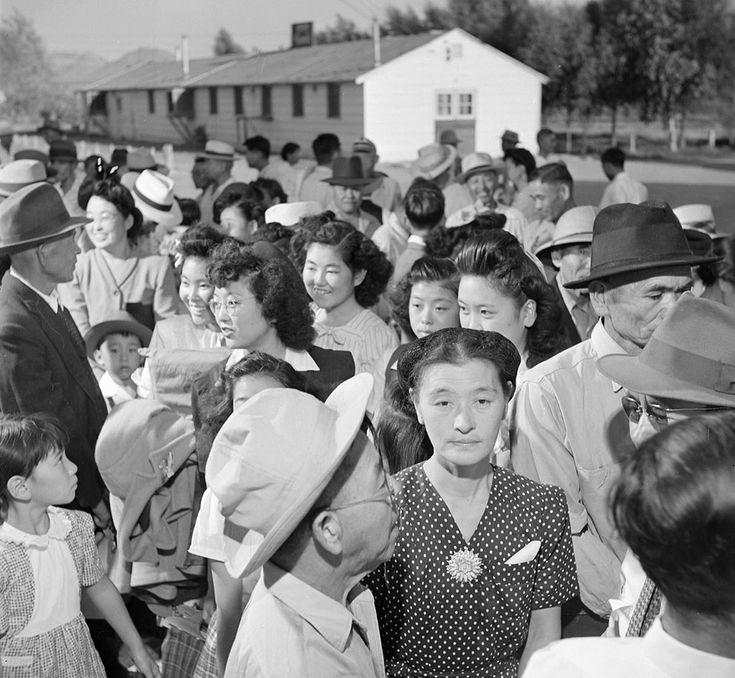 Evacuees from Arizona's Poston War Relocation Center stand in line before the departure station where they received ration books and bus tickets home in September of 1945. (NARA)