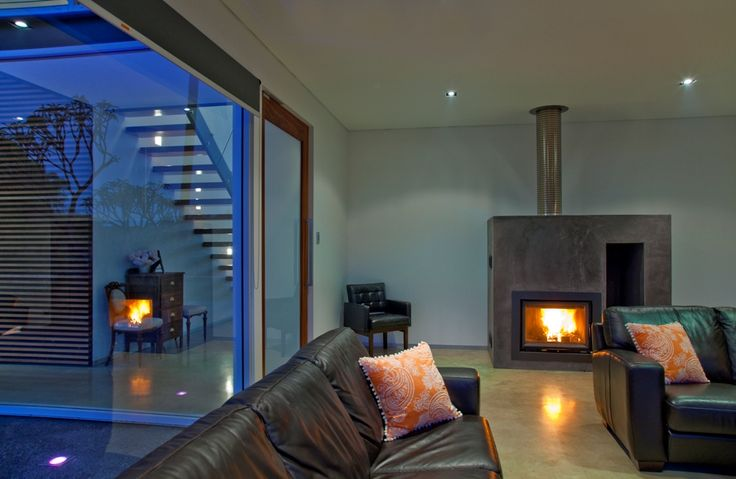 LIVING - 'salt and pepper' honed concrete floor, Chazelle firebox with glass face rendered brickwork hearth and exposed perforated stainless steel flue.