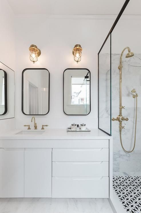 Modern black and white bathroom features a white lacquered floating washstand fitted with a square sink and a brass gooseneck faucet under two curved black mirrors illuminating dbt polished brass cage sconces.