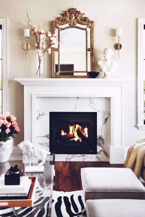 A touch of gold from a mantel mirror or table top pieces renders a warm vibe that's ideal for winter. Via My Domaine