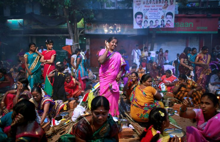 A devotee reacts to smoke as others prepare ritual rice dishes to offer to the Hindu Sun God as they attend Pongal celebrations at a slum in Mumbai, India on Jan. 15, 2015.