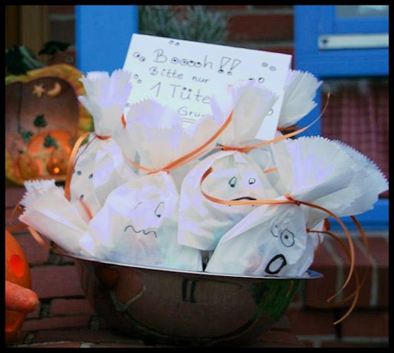 So geht's: Brottüte mit Gespenster-Gesichtern bemalen, mit Süßigkeiten füllen und oben zusammen binden.