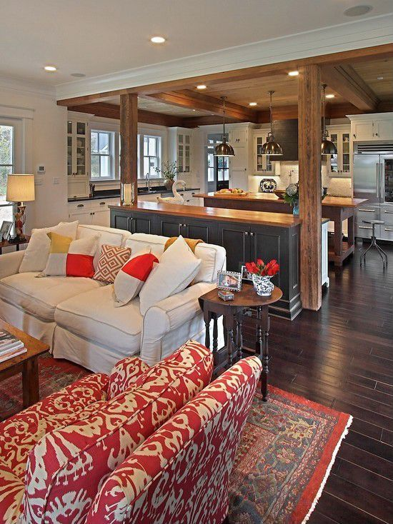 Not the rustic beams, but I like this remodel idea. Take out the sliders, replace with windows and put cabinets all the way across the back wall. French door in the family room.