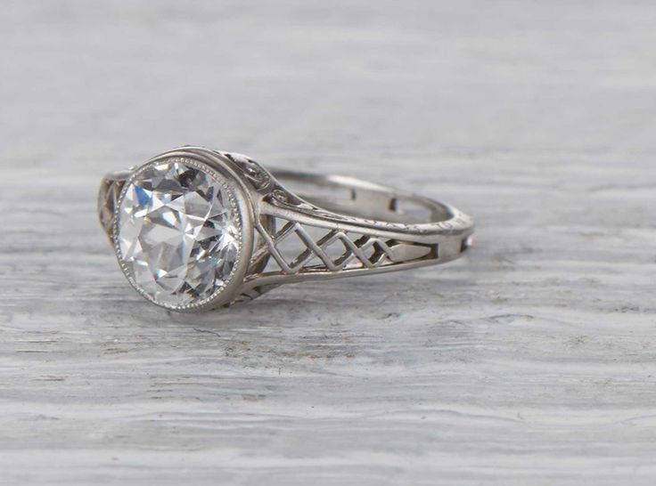 Antique Edwardian engagement ring made in platinum and centered with a GIA certified 1.30 carat old European cut diamond with F color and VS2 clarity. Circa 1914 Stunning hand done metalwork in this l