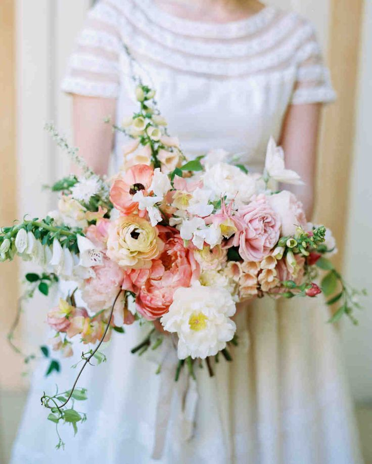 Spring Wedding Ideas from Real Celebrations   Martha Stewart Weddings - This bridal bouquet designed by Amy Merrick featured soft pastel colors and minimal greenery for a fresh spring look. The peonies, roses, and ranunculus made for a beautiful spring wedding bouquet. #weddingflowers #weddingbouquet #springweddingideas