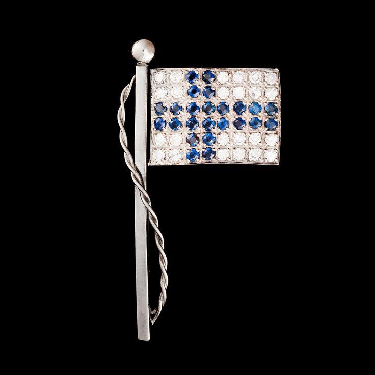 6.12 - Happy Independence Day Finland! Hyvää Itsenäisyyspäivää!   Suomen Kultaseppä, Finnish flag brooch, in 18K white gold, diamonds and 24 sapphires, 1993. | Bukowskis