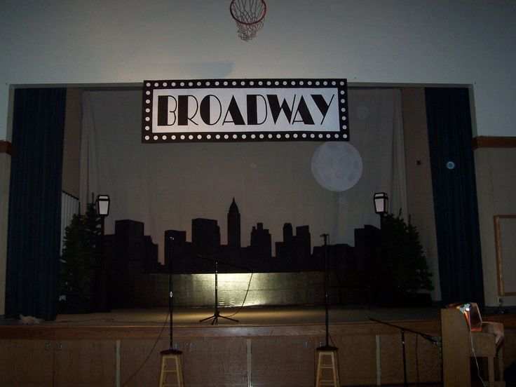 DIY Broadway theme stage - LOTS OF CARDBOARD! paint, and black duct tape - New York skyline, shimmery gold fabric, DIY street lamps, fake Christmas trees, moon, Broadway sign; scrim made out of multiple painter's cloths sewn together