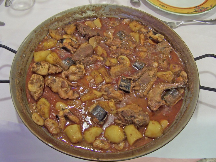 ESPARDENYÀ - Ingredientes:  400 g pato, ½ conejo, 200 g anguila, 200 g patatas, 100 g garrofón (haba), 1 tomate, 1 cebolla, 8 dientes de ajo, perejil, almendras, piñones, nuez  moscada y clavo molido. Sofreir pato y conejo. Añadir cebolla y tomate picados. Preparar picada con  ajos, perejil, almendras y piñones.   Añadirla al sofrito, con garrofón y pimentón dulce. Cocer con agua 1 h. Dejar enfriar. Agregar anguila, patatas, nuez moscada y clavo. Llevarlo a ebullición. FOTO: Rte Terele de…
