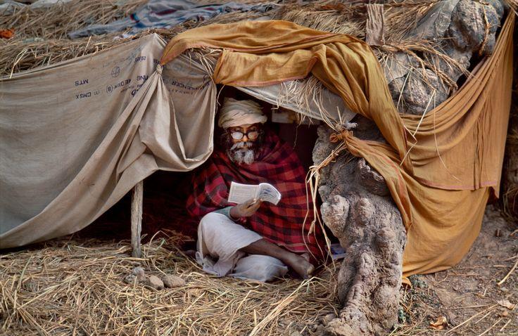 Steve McCurry, INDIA. Allahabad, Uttar Pradesh. 2001. Man sitting in make-shift tent reading. Kumbh Mela Festival