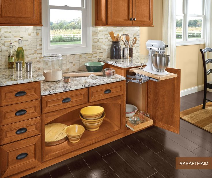 The baking station has a base mixer shelf that swings up from the base kitchen cabinet below and locks in place, then lowers out of sight. (cherry cabinets in Praline)