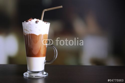 Glass of coffee on color wooden table, on dark background