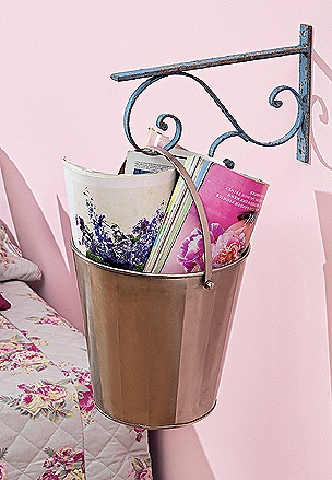 Presa na parede da cama, onde estaria o criado-mudo, a mão-francesa segura apenas o balde metálico que, assim, torna-se um revisteiro