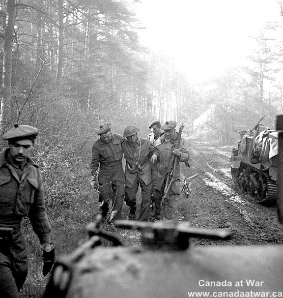 Canadians in Germany - Wounded infantry being helped back to cover. Hatten (South of), Germany, 22/23 Apr. 1945.