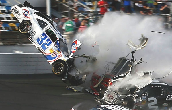 Car number 32, driven by Kyle Larson, is thrown into the air following a collision during a race at Daytona, Florida, last night. Wreckage from the crash hit a stand and injured 28 spectators.
