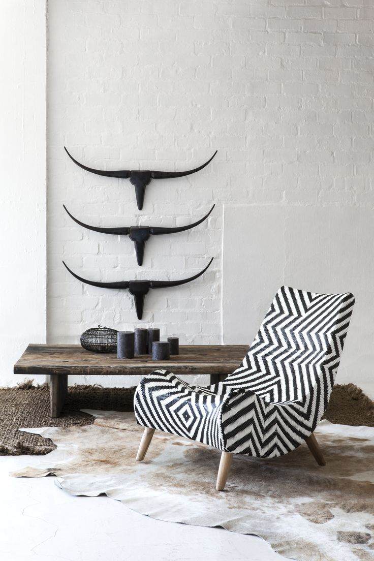 Masculine Monochromatic Room, with Chevron Lounge Chair, Cowhide Rugs, and Black Iron Longhorn Sculptures.