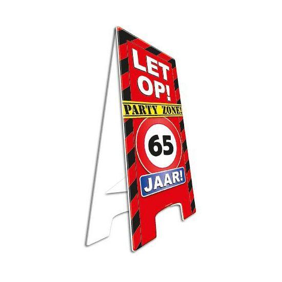 Voor een 65ste verjaardag. Waarschuwingsbord 65 jaar. Dit waarschuwingsbord is gemaakt van stevig karton en uitklapbaar. Zet het bord bij de ingang van het verjaardagsfeest en laat iedereen weten dat er een feestje is! Het bord is ongeveer 58 cm hoog.