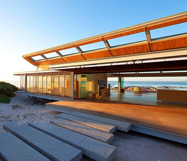 This contemporary beach house near Cape Town was designed as a single space holiday home. All of the external walls are made of sliding glass doors, which open to create a seamless view to the water!